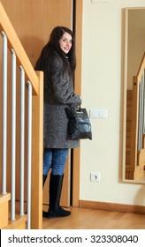 woman in coat opening door and leaving  home