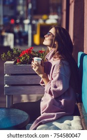 Woman in a coat sitting on the bench and drinking coffee and laughing