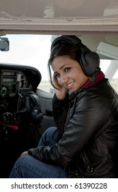 A woman in the cockpit of an airplane smiling.