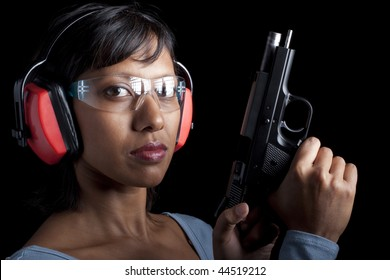 A woman cocks chambers a bullet in a pistol. She's wearing protective shooting gear. Black background.