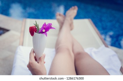 Woman with cocktail relaxing near pool. Vacation Concept.