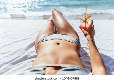 Woman with cocktail takes a sunbathe on sunbed, near the sea. Close-up view.