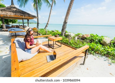 Woman with coconut relaxing in beach cafe. Tropical country holiday concept