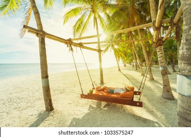 Woman with coconut relaxing on the beach between palms. Vacation concept.