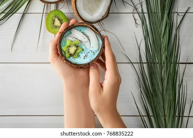 Woman with coconut shell of yummy spirulina smoothie at wooden table. Healthy vegan food concept