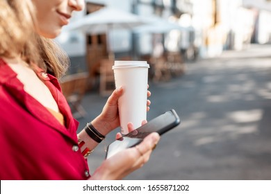 Woman with coffee cup using smart phone on the city street outdoors, close-up on phone with black screen