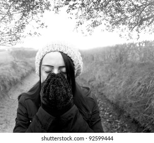 woman cold standing on country lane black and white