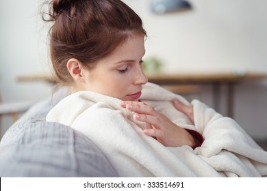 woman with a cold wrapped in a blanket with eyes closed