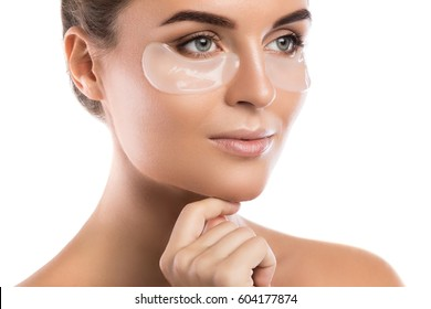 Woman with collagen pads under her eyes on white background