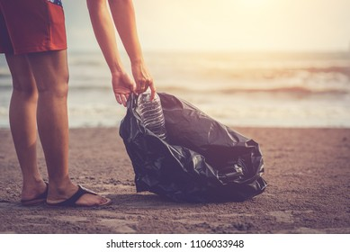 Woman are collecting garbage on the beach with the backdrop of the light of the sun. / love the sea concept.