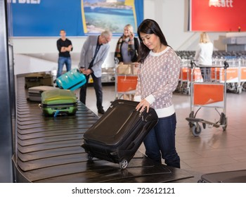 Woman Collecting Luggage At Conveyor Belt In Airport