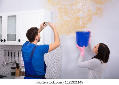 Woman Collecting Water In Blue Bucket From Damaged Ceiling While Repairman Taking Photograph On Mobilephone