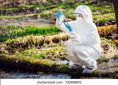 Woman collects water in a test tube. Ecology and environmental pollution concept.