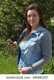 Woman College/University Student Outdoors Holding a Cell Phone or Mobile Phone  Vertical image shows a young female college university student outdoors with a cell phone or mobile phone.