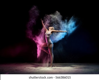 Woman in color dust cloud streches up gracefully