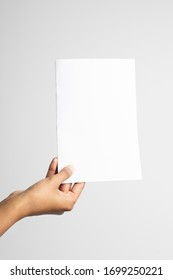 Woman of color holding an a5 or half letter-sized blank mockup.