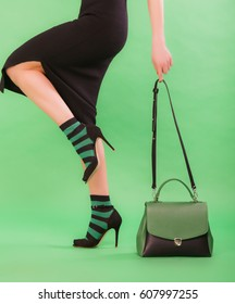 Woman in colored socks holding green and black handbag on a green background