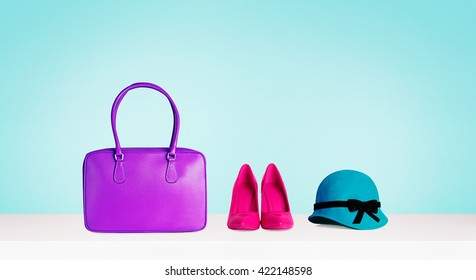 Woman colorful accessories isolated on aqua blue background. Purple bag, red heels shoes and green hat.