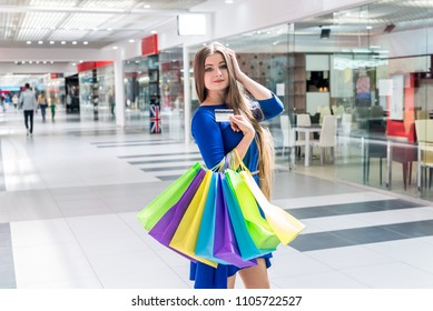 Woman with colorful bags and credit card in mall