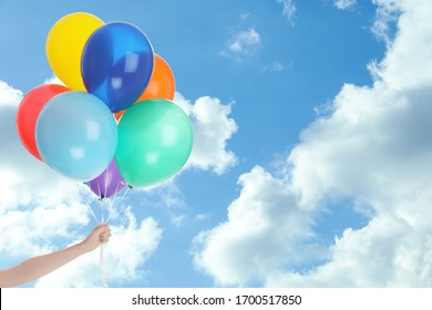 Woman with colorful balloons outdoors on sunny day, closeup. Space for text