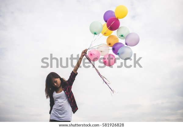 Woman with colorful balloons outside blue sky background.