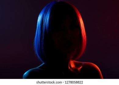 Woman in colorful bright lights posing in studio, portrait of beautiful sexy girl.
