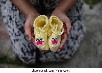A woman with colorful child socks on her hands, concept of a woman expecting child in her life