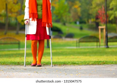 woman in colorful clothes standing on crutches in the autumnal park