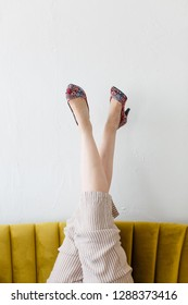 Woman in colorful heels kicking feet up relaxing