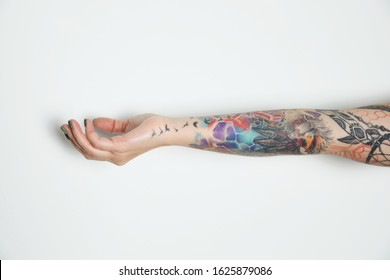 Woman with colorful tattoos on arm against white background, closeup