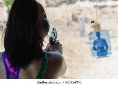 Woman in colorful top and ear muffs aiming handgun at practice target, with focus on pistol as bullet shell flies out of the gun
