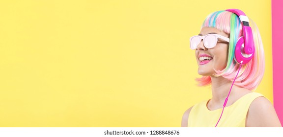 Woman in a colorful wig with headphones listening to music on a split yellow and pink background