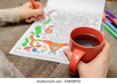 Woman coloring an adult coloring book and drinking tea, new stress relieving trend, mindfulness concept, married woman