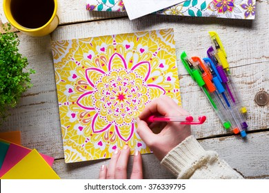 Woman coloring an adult coloring book, new stress relieving trend, mindfulness concept, hand detail