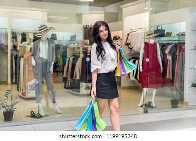 Woman with colourful shopping bags posing before dress store