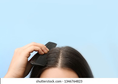 Woman with comb and dandruff in her dark hair on color background, closeup. Space for text