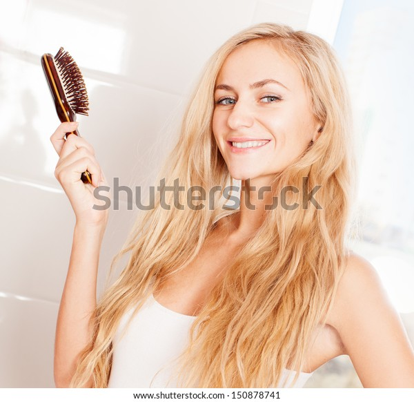 Woman combing in bathroom. Female with hairbrush
