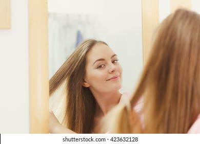 Woman combing brushing her long smooth hair in bathroom, looking in mirror. Girl taking care refreshing her hairstyle. Haircare concept.