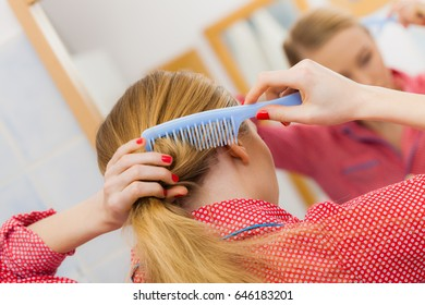 Woman combing brushing her long blonde smooth hair in bathroom, looking in mirror. Teen girl taking care refreshing her hairstyle in morning. Haircare concept.