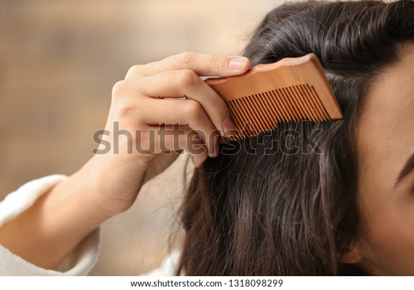 Woman combing hair on blurred background, closeup
