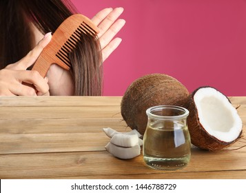 Woman combing her healthy hair and natural coconut oil on wooden table against pink background