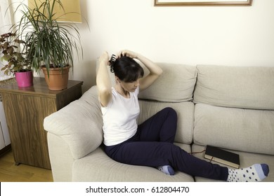 Woman combing next to a book on a sofa next to some green plants