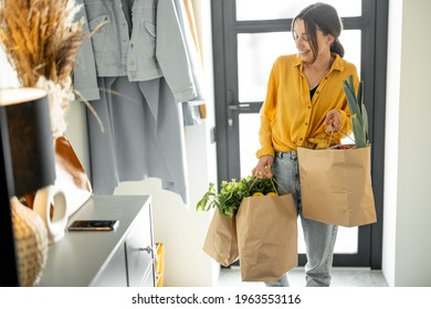 Woman comes home with bags full of fresh groceries, shopping healthy food in eco-packaging. Concept of buying food online and delivering it home - Shutterstock ID 1963553116