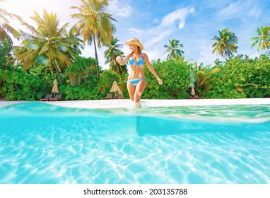 Woman comes into water on the beach, beautiful tropical island, luxury summertime vacation, happiness and freedom concept