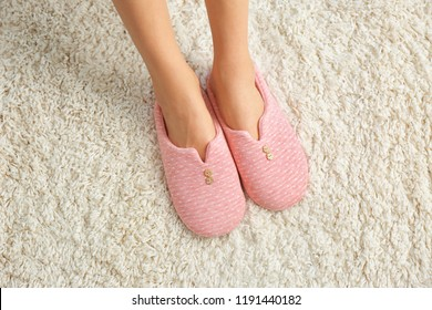 Woman in comfortable slippers on carpet, closeup. Floor heating