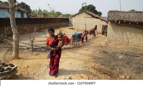 woman coming out of her mud house with child in lap  Daldali Village Rural India Dhanbad / Jharkhand state of India / at Jharkhand / India clicked on 10 February 2018