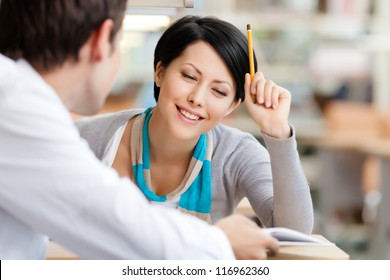 Woman communicates with handsome man showing her something in the book at the library
