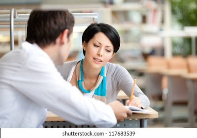 Woman communicates with young man showing her something in the book sitting at the desk at the library