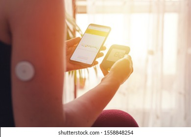 Woman comparing result of glucose level check on the traditional glucometer and on the mobile phone reading from modern technology remote sensor mounted on her forehand