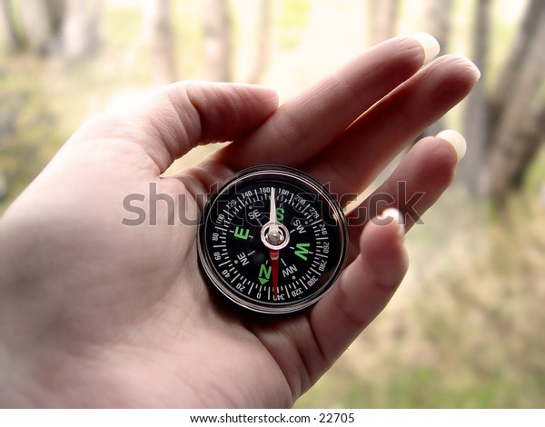Woman with a compass in her hand in the woods